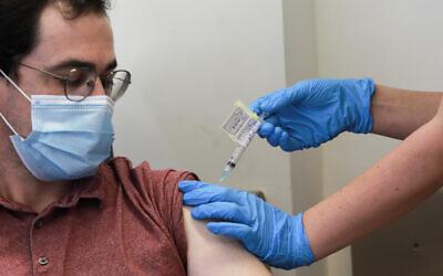 Aner Ottolenghi receives the Israeli-developed Coronavirus vaccination at the Hadassah Ein Karem hospital in Jerusalem on November 1, 2020. (Yonatan Sindel/Flash90)