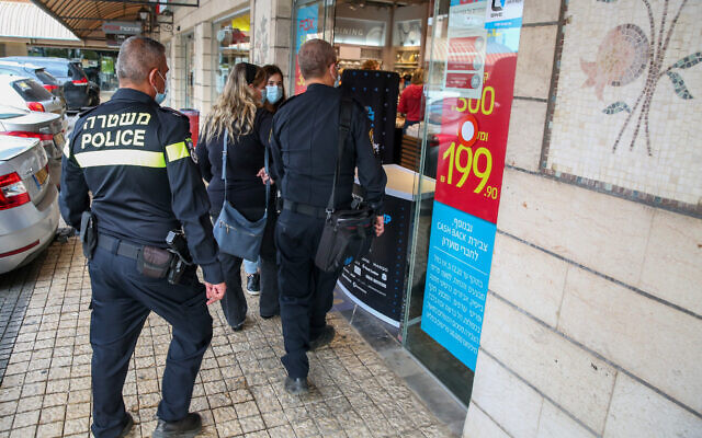 Police officers patrol outside shops during a national lockdown due to the coronavirus outbreak, in Rosh Pina on November 8, 2020. (David Cohen/Flash90)