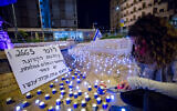 """People stand next to LED candles placed by activists from the """"Darkenu"""" movement in memory of Israel's coronavirus victims, near the prime minister's official residence in Jerusalem on November 8, 2020. The poster says the number of dead has reached the level of those killed in the 1973 Yom Kippur War and calls for a commission of inquiry. (Olivier Fitoussi/Flash90)"""