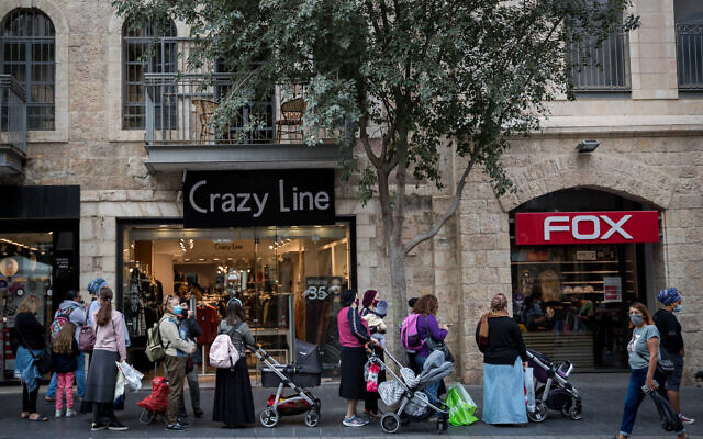 People stand in line outside stores in Jerusalem after they were permitted to reopen following a national lockdown due to the coronavirus outbreak, on November 8, 2020. (Yonatan Sindel/Flash90)
