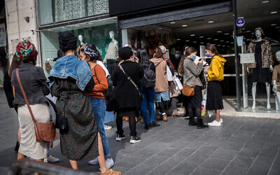 People shop on the first day of the reopening of street shops on Jaffa Street in downtown Jerusalem on November 8, 2020. (Yonatan Sindel/Flash90)