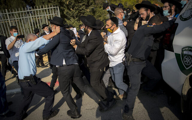 Israeli police officers try to contain a crowd of yeshiva students during the funeral of late Rabbi David Feinstein on November 9, 2020 in Jerusalem. (Yonatan Sindel/Flash90)