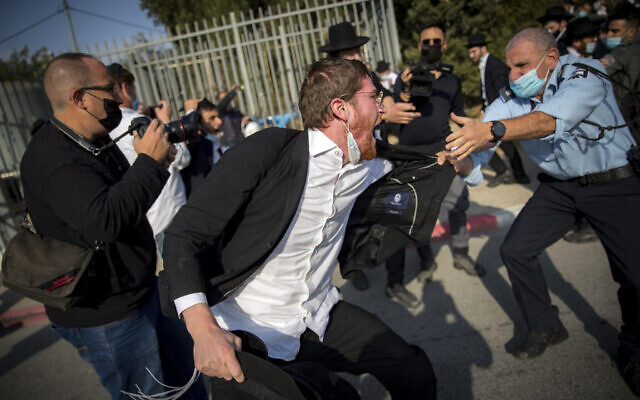 Israeli police officers try to contain a crowd of yeshiva students during the funeral of late Rabbi David Feinstein on November 9, 2020, in Jerusalem. (Yonatan Sindel/Flash90)