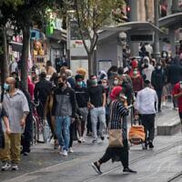 People wearing face masks take cover from the rain on Jaffa Street in downtown Jerusalem, on November 11, 2020. (Yonatan Sindel/Flash90)