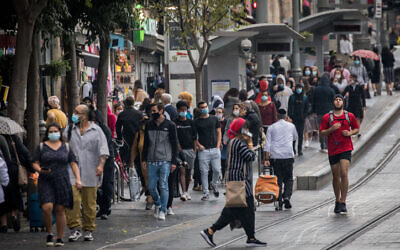 People wearing face masks take cover from the rain on Jaffa Street in downtown Jerusalem, on November 11, 2020. (Yonatan Sindel/Flash90)