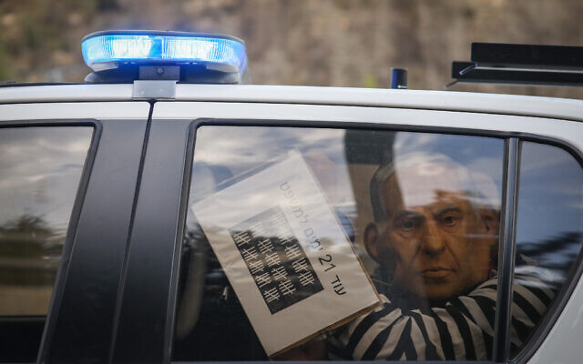 A protester wearing a mask depicting Prime Minister Benjamin Netanyahu and wearing a prisoner's uniform is detained during a demonstration on November 14, 2020 (Yonatan Sindel/Flash90)