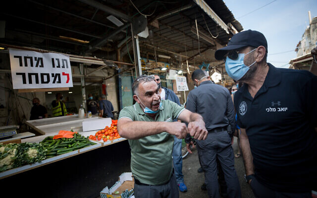 Local shop owners open their stands at the Carmel Market in protest against the ongoing closure of the market, Tel Aviv, November 17, 2020. (Miriam Alster/Flash90)
