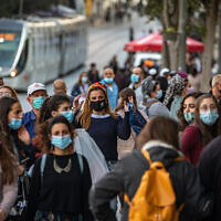 Israelis wearing face masks walk on Jaffa Street in downtown Jerusalem, on November 19, 2020. (Olivier Fitoussi/Flash90)