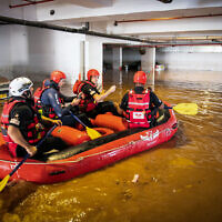 Israeli firefighters search for people in a flooded parking in Ness Ziona, November 21, 2020 (Yossi Aloni/Flash90)