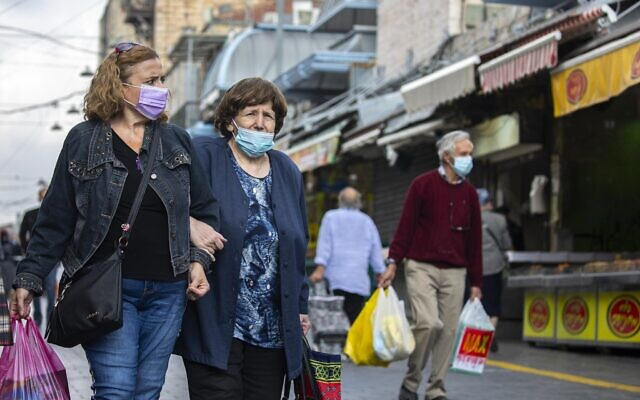Jerusalem residents wearing a face mask shop for grocery at the Mahane Yehuda market in Jerusalem on November 22, 2020, as Israel steps out of coronavirus lockdown and rolls back restrictions. (Olivier Fitoussi/Flash90)
