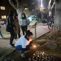 A woman light candles in memory of women murdered in domestic violence, at a street memorial on Rothschild Boulevard, Tel Aviv, ahead of International Day of Violence Against Women. November 24, 2020. (Miriam Alster/FLASH90)