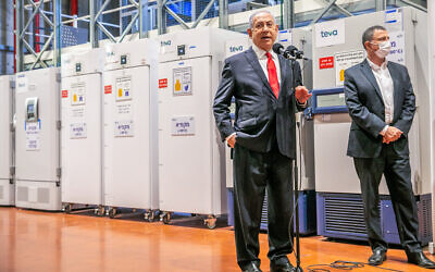 Prime Minister Benjamin Netanyahu, left, and Health Minister Yuli Edelstein visit the Teva Pharmaceuticals logistics center in Shoham, where coronavirus vaccines would be stored in freezers and then distributed, November 26, 2020. (Yossi Aloni/Flash90)
