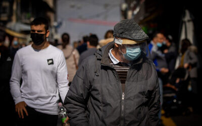 People wearing face masks shop at the Mahane Yehuda market in Jerusalem on November 27, 2020. (Yonatan Sindel/Flash90)