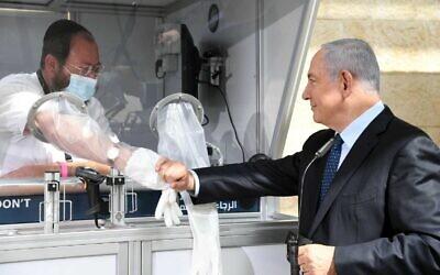 Prime Minister Benjamin Netanyahu visits a new coronavirus testing station at Ben Gurion Airport on November 9, 2020. (Haim Zach/GPO