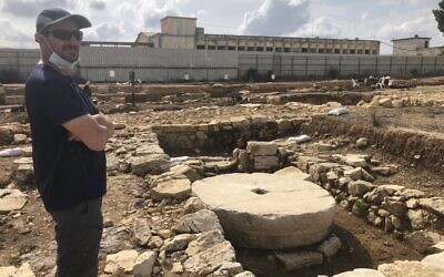 Excavation director Yevgeny Aharonovich stands next to an unused Second Temple-era olive press at the ancient settlement of Kafr Murr, today a neighborhood of Beit El, November 3, 2020. (Amanda Borschel-Dan/ToI)