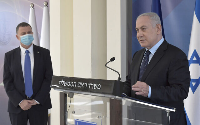 Prime Minister Benjamin Netanyahu delivers a televised statement on the signing of a deal to purchase Pfizer's coronavirus vaccine, at IDF military headquarters in Tel Aviv, November 13, 2020. At left is Health Minister Yuli Edelstein. (Kobi Gideon/GPO)