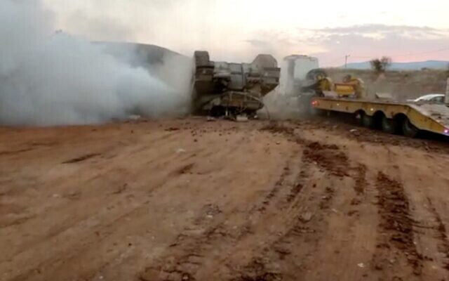 An IDF tank flips over while driving onto a transport truck in the Jordan Valley on Novermber 22, 2020. (Screen capture)