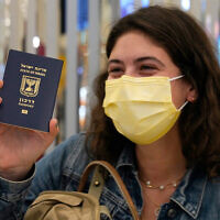 An Israeli passenger from a flydubai flight from Tel Aviv waves her Israeli passport on arrival at Dubai International Airport in the United Arab Emirates, November 26, 2020. (AP Photo/Jon Gambrell)