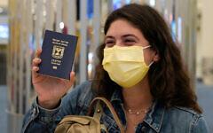 An Israeli passenger from a flydubai flight from Tel Aviv waves her Israeli passport on arrival at Dubai International Airport in the United Arab Emirates, Nov. 26, 2020. (AP Photo/Jon Gambrell)