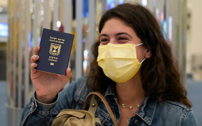 An Israeli passenger from a flydubai flight from Tel Aviv waves her Israeli passport on arrival at Dubai International Airport in the United Arab Emirates, November 26, 2020. (AP Photo/Jon Gambrell)