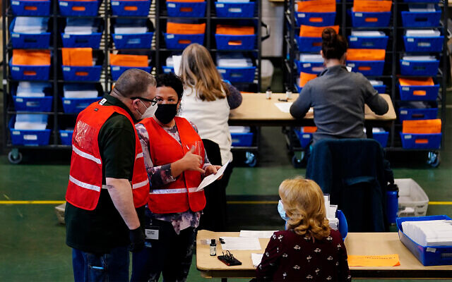 Election workers check mail-in and absentee ballots for the 2020 General Election in West Chester, Pennsylvania, Nov. 3, 2020. (AP Photo/Matt Slocum)