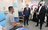 Prime Minister Benjamin Netanyahu (C) and Defense Minister Benny Gantz (R) speak with Segev Harel, the first volunteer for trials for an experimental Israeli coronavirus vaccine, at Sheba Medical Center, November 1, 2020. (Ariel Hermoni/Defense Ministry)