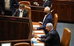 Benny Gantz, center, and Benjamin Netanyahu, right, at the Knesset on November 10, 2020. (Shmulik Grossman/Knesset spokesperson)