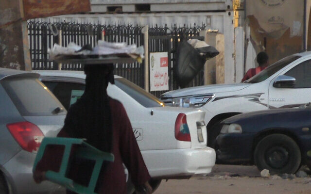 A woman carrying a tray on her head in Khartoum, Sudan, November 2020. (Ziv Genesove)