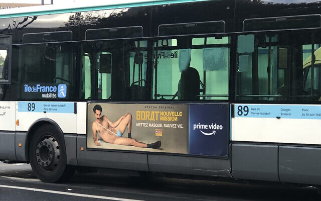 """A RATP bus with a billboard of Sacha Baron Cohen wearing a ring with the word """"Allah"""" on it moves through Paris, France on November 2, 2020. (Courtesy of @firehairedreamr/Twitter via JTA)"""