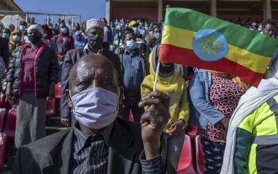 A man holds a national flag as he waits in the stands to give blood at a blood drive in support of the country's military, at a stadium in the capital Addis Ababa, Ethiopia, November 12, 2020. (AP Photo/Mulugeta Ayene)