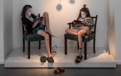 Artist Inbal Hoffman's children pose in Ticho House chairs as part of her new exhibit, 'Mundane Heights,' which opened virtually on October 29, 2020. (courtesy, Israel Museum)