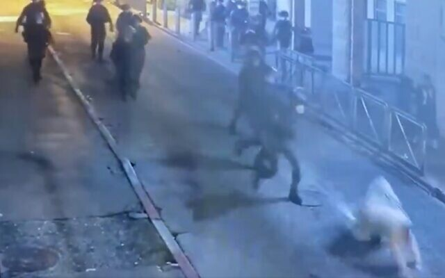 Border police officer shoves a man to the ground in the ultra-Orthodox neighborhood of Mea Shearim, April 4, 2020 (Screen grab)