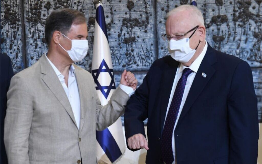 Eytan Stibbe and Israeli president Reuven Rivlin bump elbows at a ceremony celebrating Stibbe's planned trip to the International Space Station, November 16, 2020 (Mark Neyman/GPO)