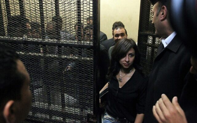 One of fourteen Egyptians, who refused to be identified, on trial on charges of receiving illicit foreign funds to operate unlicensed NGOs, leaves a cage in a court room in the capital Cairo, March 8, 2012. (Photo by Khaled DESOUKI / AFP)