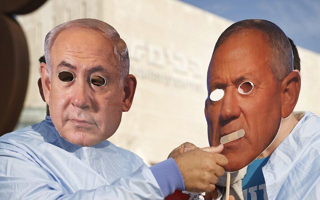 Israelis wearing masks of Prime Minister Benjamin Netanyahu, left, and Defense Minister Benny Gantz at a protest in Tel Aviv on  December 2, 2020. (Jack Guez/AFP)