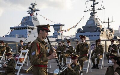 An Israeli military band rehearses ahead of a ceremony marking the arrival of the first of four new German-built Sa'ar 6 ships (back left), at the naval base in Haifa on December 2, 2020. (Heidi Levine/Pool/AFP)