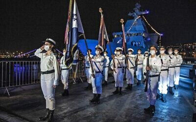 Israeli sailors take part in a ceremony marking the arrival of the first of four new German-built Sa'ar 6 ships (back left), at the naval base in Haifa on December 2, 2020. (Heidi Levine/Pool/AFP)