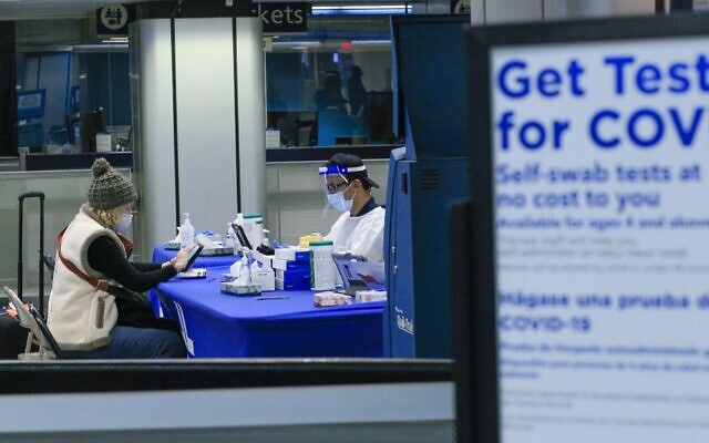 A woman gets a self coronavirus test at a free walk-up COVID-19 testing site inside Penn Station in New York City, December 5, 2020. (Kena Betancur/AFP)