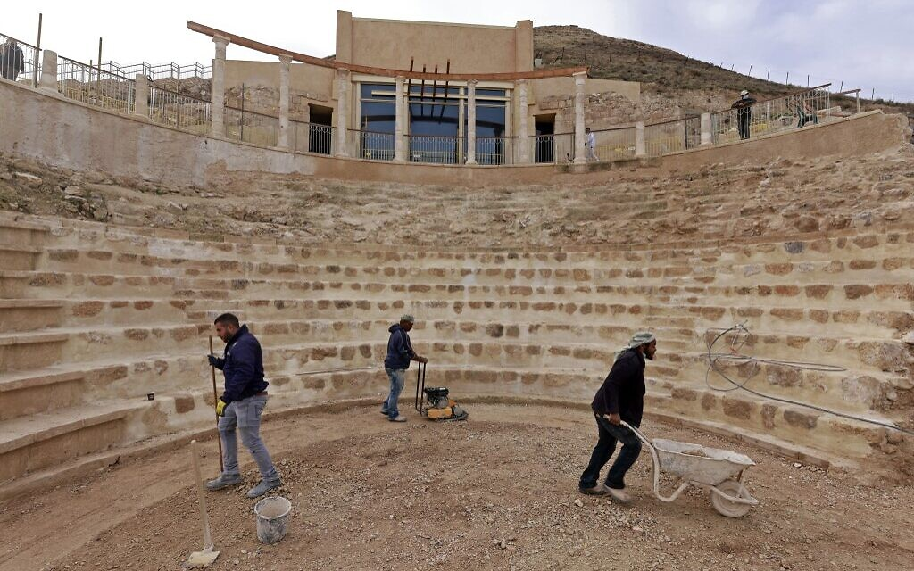 Workers keep flat the restored floor of the ancient theatre built by Herod the Great between 23-15 BCE in the Judaean desert, southeast of Bethlehem in the West Bank, on December 7, 2020.  (Menahem KAHANA / AFP)