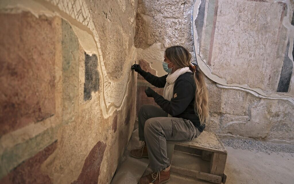 A conservator of the Israel Antiquities Authority restores ancient frescoes at the arches corridor leading to the Herodium palace built by Herod the Great between 23-15 BCE in the Judaean desert, southeast of Bethlehem (Menahem KAHANA / AFP)