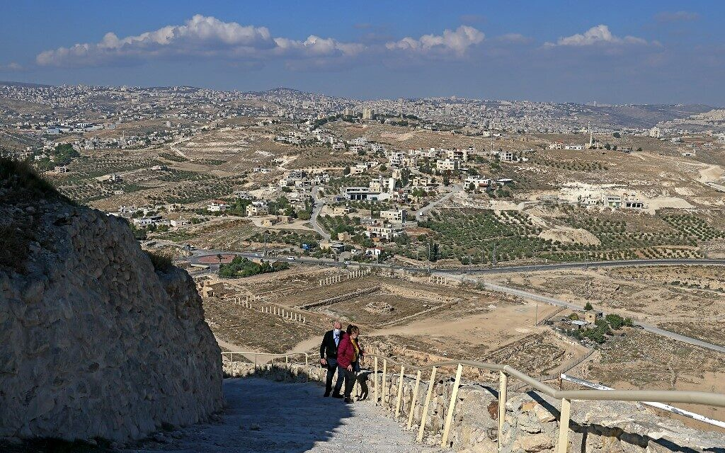 A couple climbs the steps leading to the ancient Herodium palace built by Herod the Great between 23-15 BCE in the Judaean desert, southeast of Bethlehem on November 24, 2020. (Menahem KAHANA / AFP)