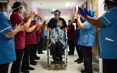 Margaret Keenan (C) is applauded by staff as she returns to her ward after becoming the first person in the United Kingdom to receive the Pfizer-BioNtech COVID-19 vaccine at University Hospital in Coventry, England, on December 8, 2020. (Jacob King/Pool/AFP)