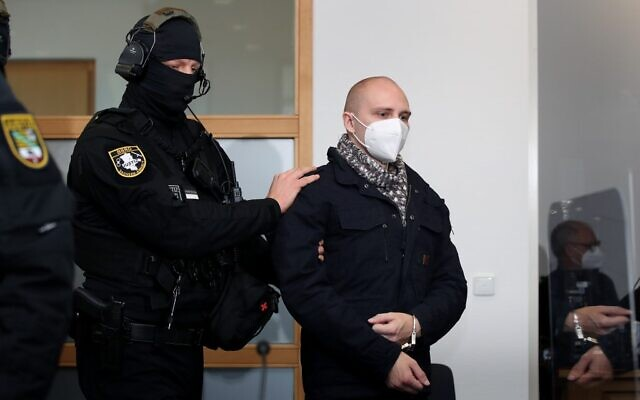 Stephan Balliet, who is accused of shooting dead two people after an attempt to storm a synagogue in Halle an der Saale, eastern Germany, is led by a police officer into the courtroom for the start of the 24th day of his trial on November 3, 2020 at the district court in Magdeburg, eastern Germany. (Ronny Hartmann / AFP)