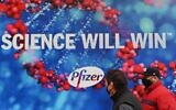 People wearing protective face masks walk past the Pfizer Inc. headquarters on December 9, 2020 in New York City. (Angela Weiss / AFP)