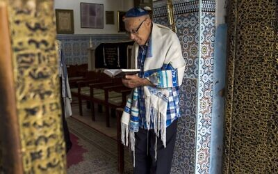 """In this file photo taken on October 13, 2017, Moroccan Jews and Israeli Jewish tourists participate in a religious ceremony to observe the holiday of Sukkot (the Feast of the Tabernacles) at a synagogue in the """"Mellah"""" Jewish quarter of the Medina in Marrakesh (FADEL SENNA / AFP)"""