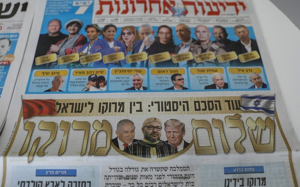 This picture taken on December 11, 2020 in Jerusalem shows Israeli newspapers' front page titles about the announcement that Israel is to establish diplomatic relations with Morocco.(AHMAD GHARABLI / AFP)
