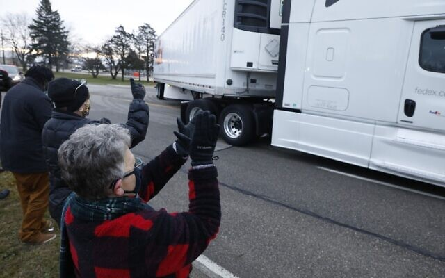 Nancy Galloway (L) and Susan Deur cheer as trucks carrying the first shipment of the COVID-19 vaccine that is being escorted by the US Marshals Service, leave Pfizer's Global Supply facility in Kalamazoo, Michigan, on December 13, 2020. (JEFF KOWALSKY / AFP)