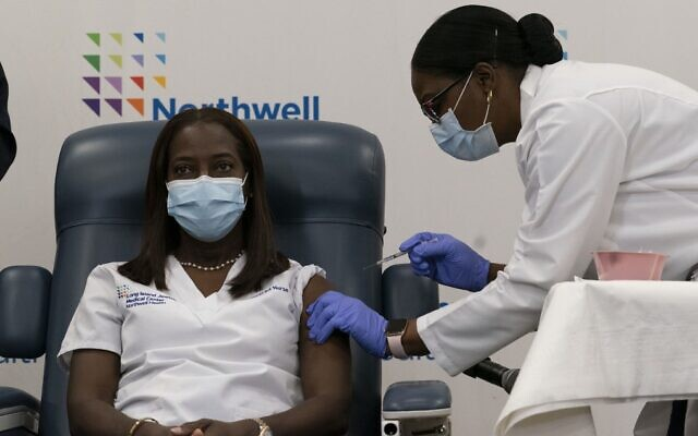 Illustrative: Sandra Lindsay (L), a nurse, is inoculated with the COVID-19 vaccine by Dr. Michelle Chester, at Long Island Jewish Medical Center, on December 14, 2020, in the Queens borough of New York. (Mark Lennihan/Pool/AFP)