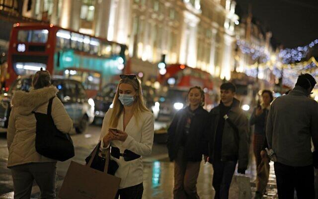 Shoppers pass under the Christmas lights on Regents Street in central London on December 14, 2020. (Tolga Akmen/AFP)