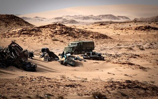 A Moroccan army vehicle drives past car wreckages in Guerguerat located in the Western Sahara on November 24, 2020, after the intervention of the royal Moroccan armed forces in the area. (Fadel SENNA / AFP)